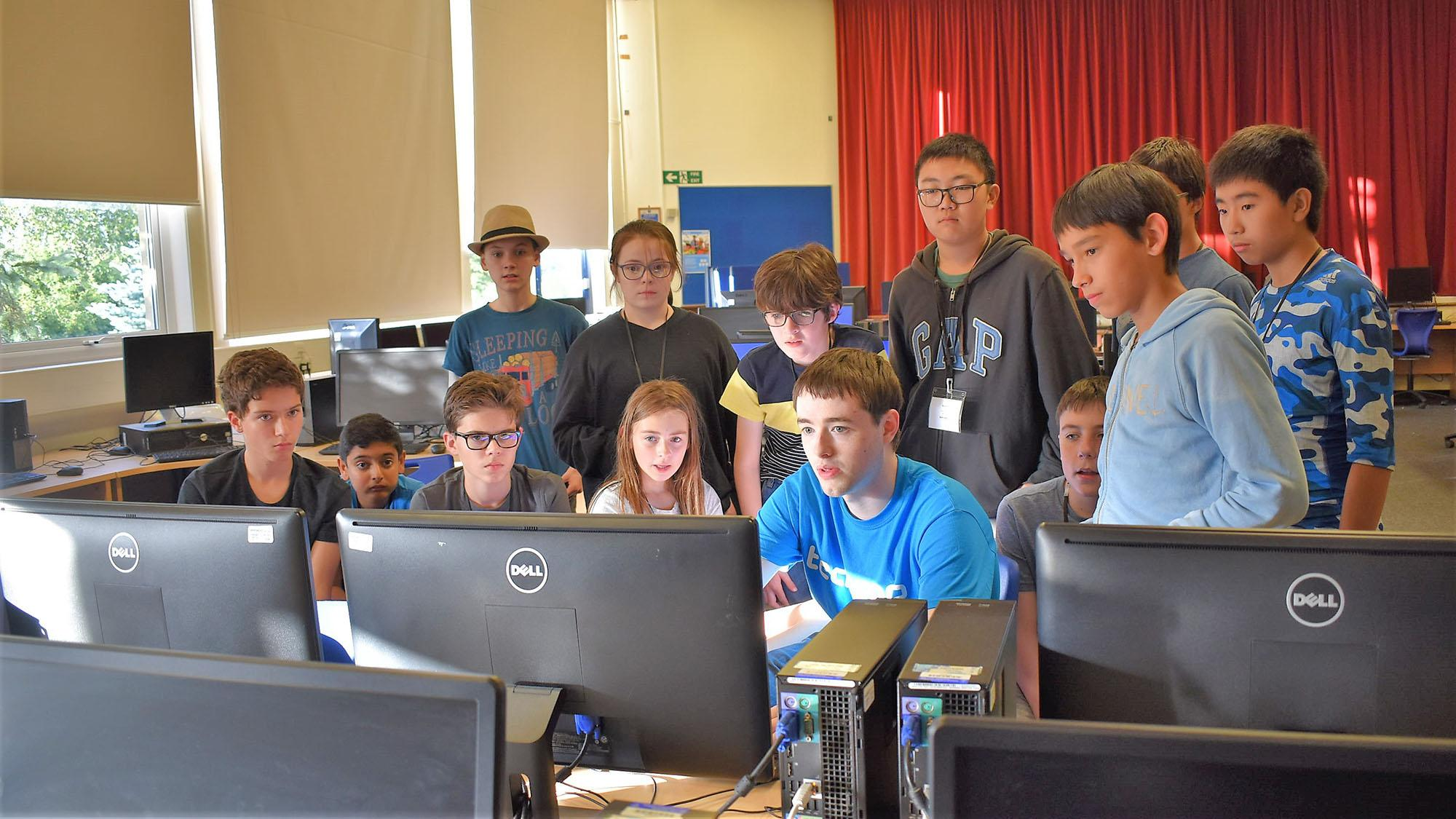 Teens and Tech Camp tutor gathered around a computer screen