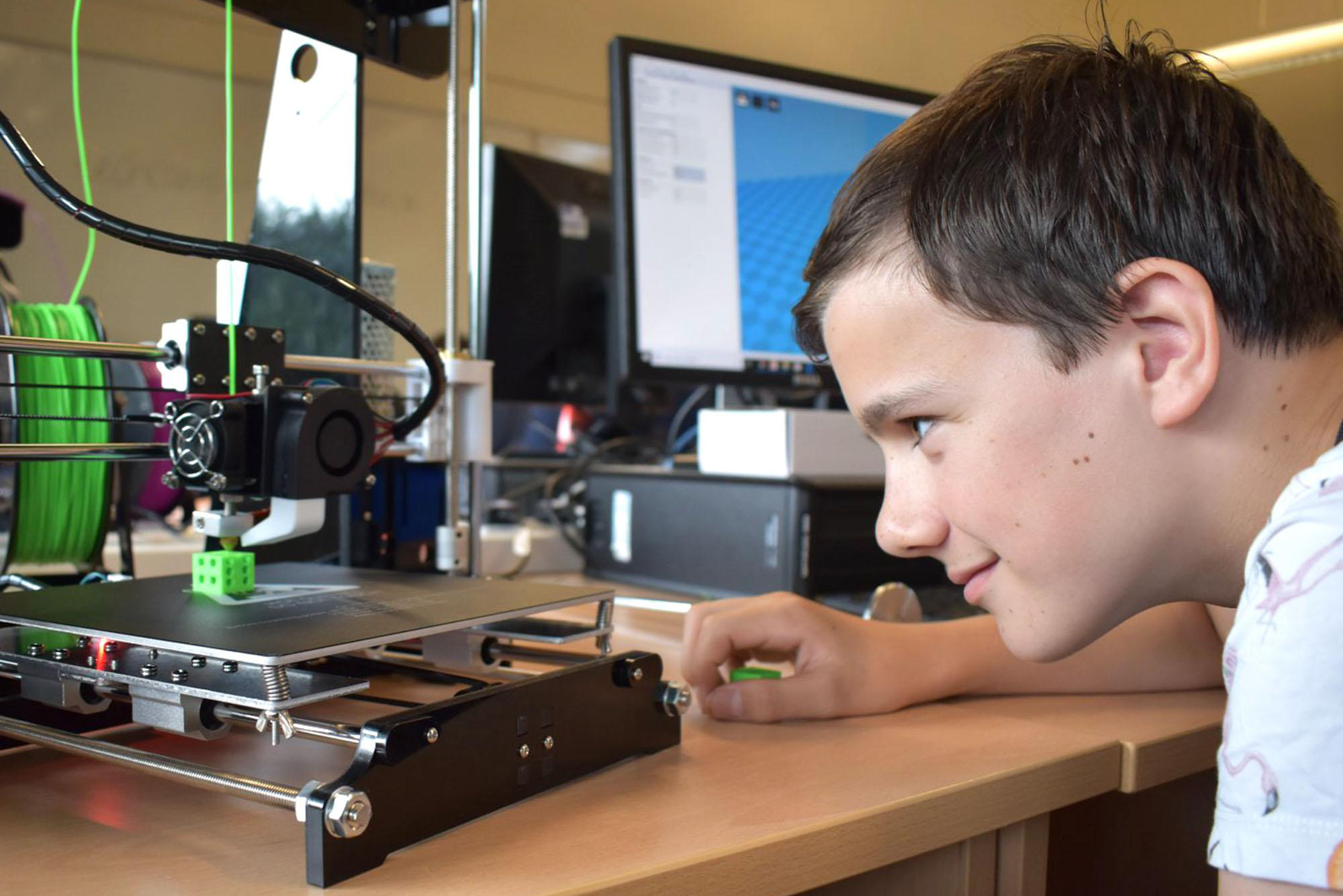 Teen boy looking at 3D printer