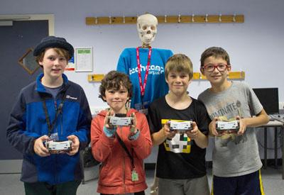 Group of students and teacher at a robotics Summer camp showing off their creations
