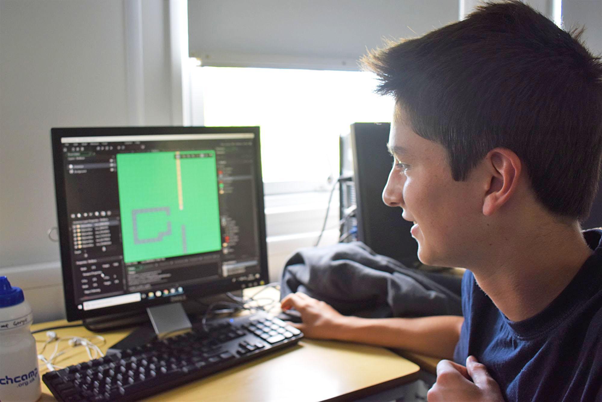 Teen boy looking at 3D printer