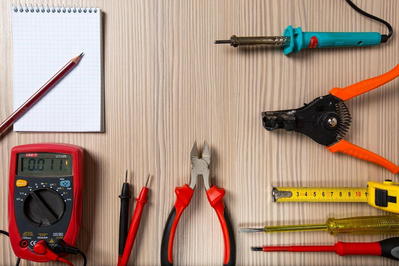 Tools on a desk including a multimeter, soldering iron and screwdrivers